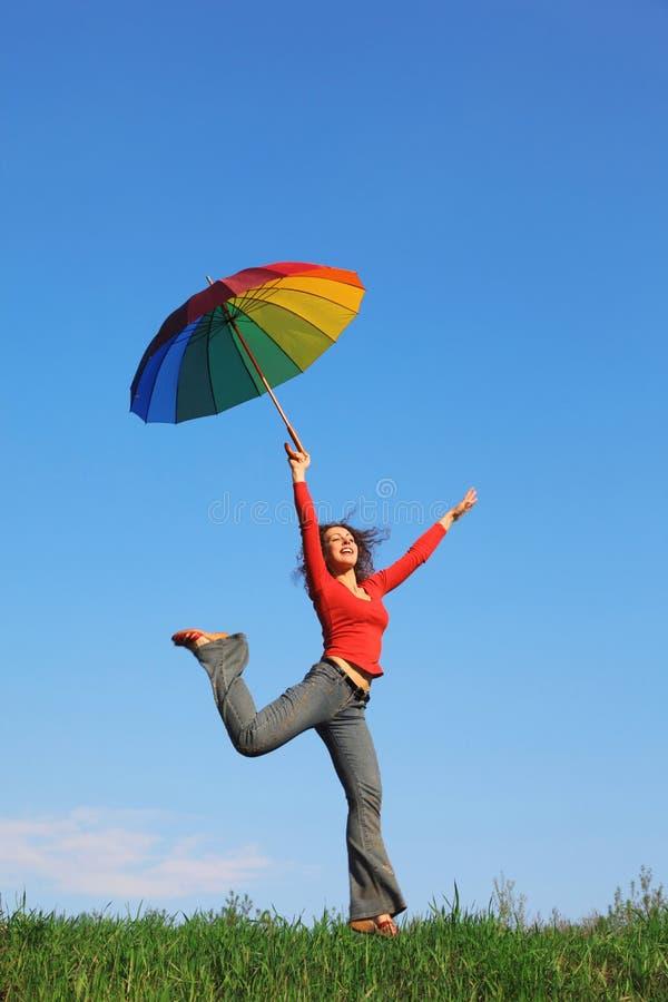 La fille sautant par-dessus l'herbe avec le parapluie coloré photos libres de droits