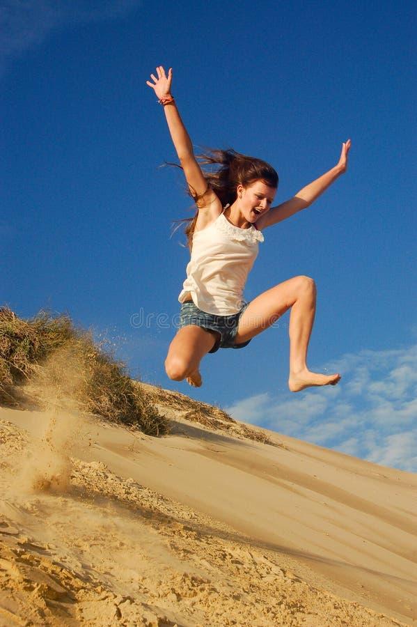 La fille sautant sur la plage photos libres de droits