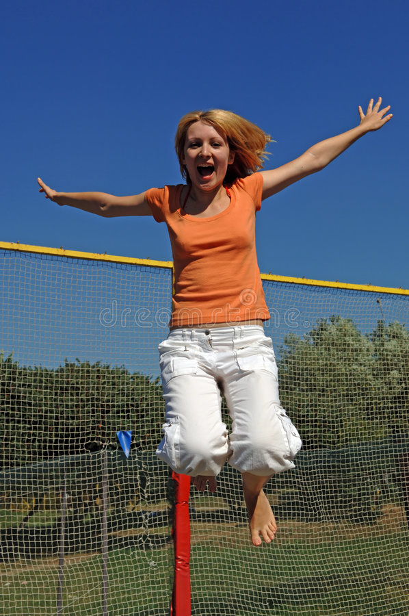 La fille sautant sur le tremplin photographie stock