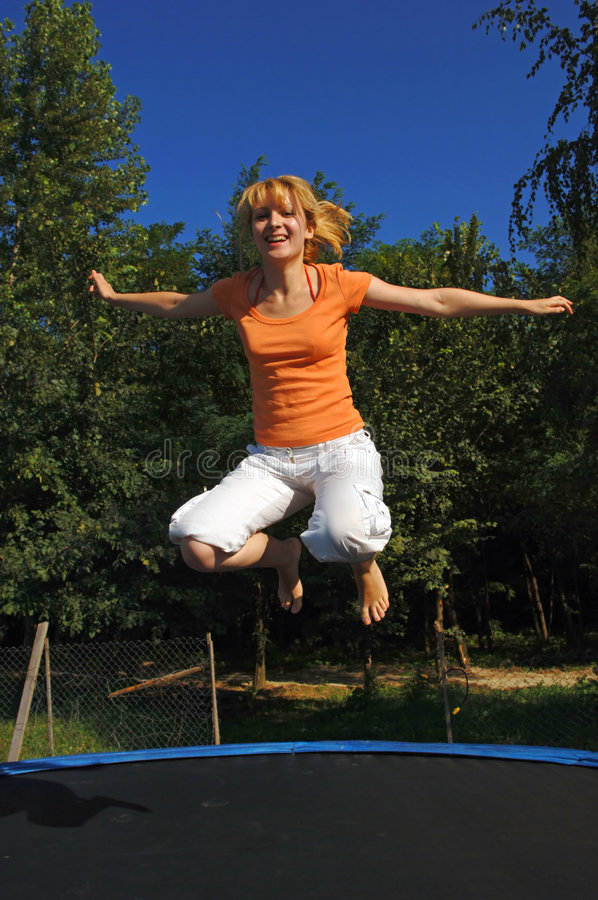 La fille sautant sur le tremplin photos stock