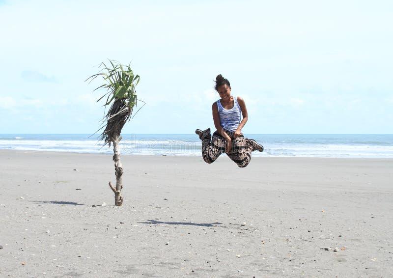 La fille sautant sur la plage photographie stock libre de droits