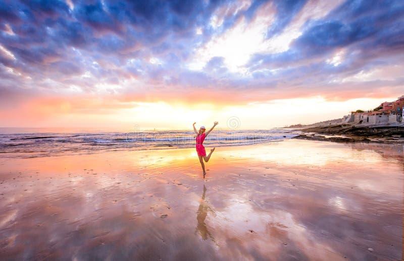 La fille sautant sur une plage dans le ressac de Taghazout et le village de pêche, Agadir, Maroc photos libres de droits