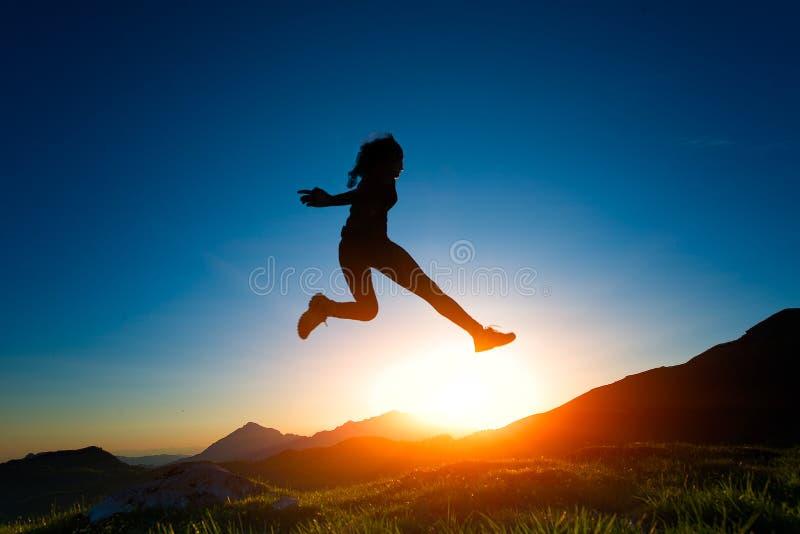 La fille saute pendant un coucher du soleil dans les montagnes photo stock