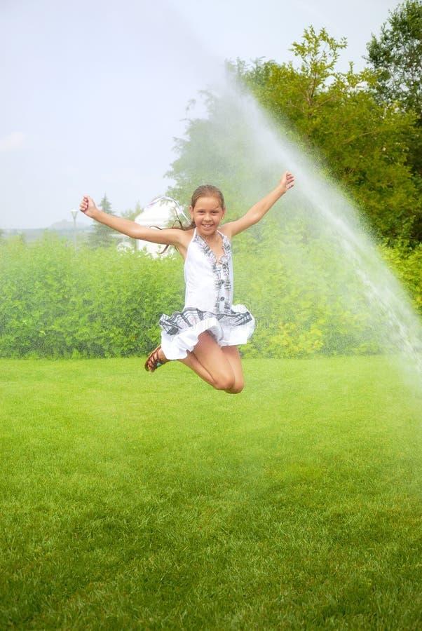La fille saute sous des baisses de jet photographie stock libre de droits