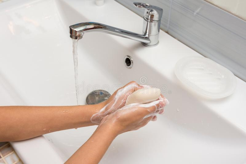 La fille savonne soigneusement ses mains avec du savon, plan rapproché photographie stock