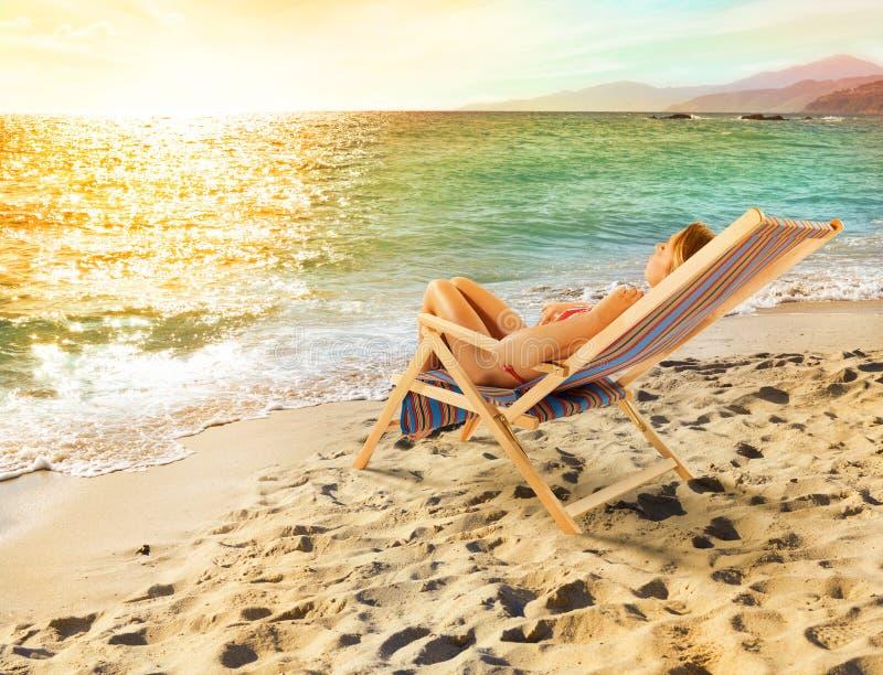 La fille se bronze sur une chaise de plate-forme sur une belle plage images stock
