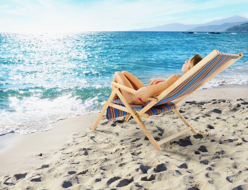 La fille se bronze sur une chaise de plate-forme sur une belle plage images libres de droits