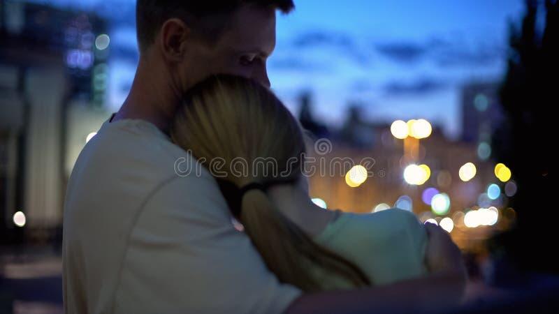 La fille se penche sur l'épaule de type, étreindre, regardant la ville de nuit, proximité, sécurité photographie stock libre de droits