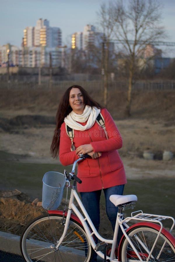 La fille se penche sur un vélo garé Repos sur le cycle de ressort images libres de droits