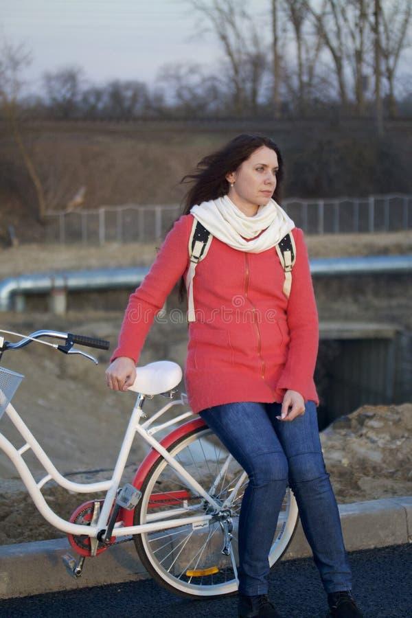 La fille se penche sur un vélo garé Repos sur le cycle de ressort image libre de droits