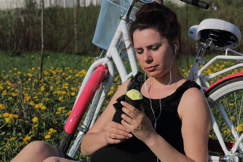 La fille se repose sur le pr? de ressort Il s'assied à côté du vélo, mange la crème glacée et écoute la musique Les pissenlits fl image stock
