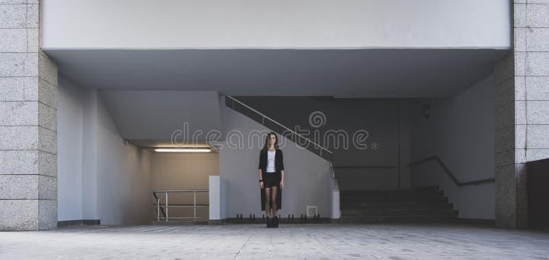 La fille se tient à un passage pour piétons souterrain La géométrie de la ville moderne L'atmosphère en pierre photos libres de droits