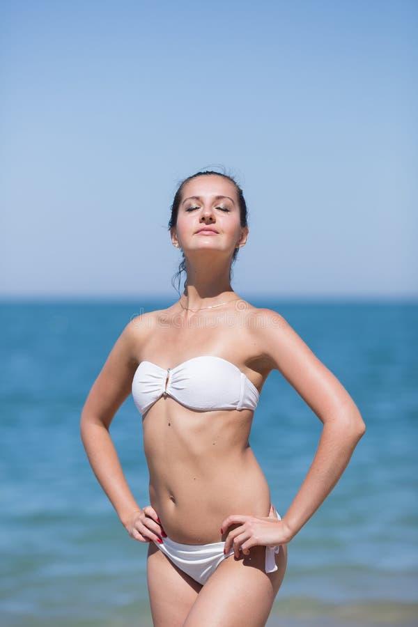 La fille se tient avec des bras sur les hanches contre la mer images stock
