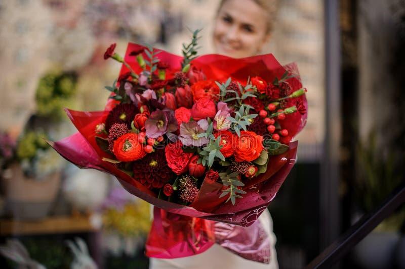 La fille se tient avec un bouquet complètement rouge photographie stock libre de droits