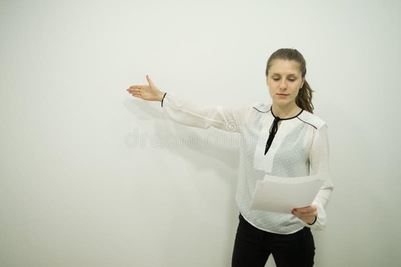 la fille se tient contre un mur blanc et lit un rapport, ayant abaissé ses yeux dans lui, tient des feuilles dans une main, indiq image libre de droits