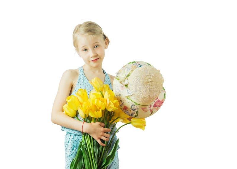 La fille se tient dans sa main droite qu'un bouquet des tulipes jaunes a isolée sur un fond blanc photos stock