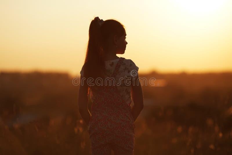 La fille se tient et examine la distance images stock