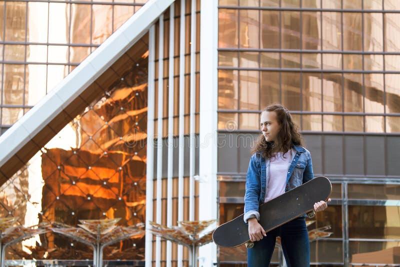 La fille se tient près d'un bâtiment tenant un panneau de patin dans une ville près d'un édifice haut images stock