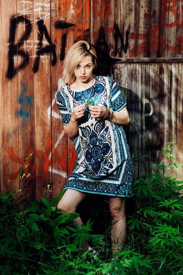 La fille se tient prêt le mur avec le cannabis dans des ses mains photographie stock