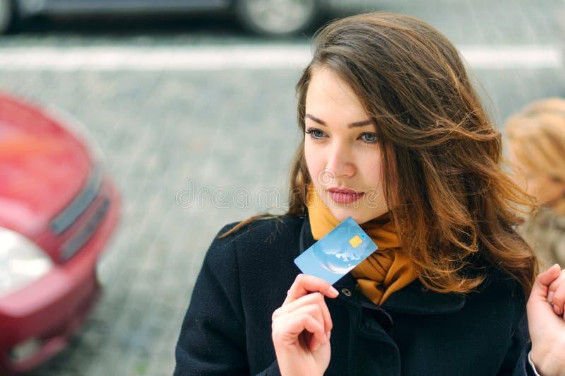 La fille se tient sur une rue de ville avec une carte de crédit photos stock