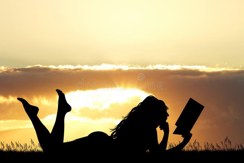 La fille se trouvant sur l'herbe lit un livre au coucher du soleil image stock