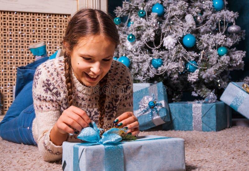 La fille se trouve près d'un arbre de Noël avec le boîte-cadeau de cadeau de Noël photographie stock libre de droits