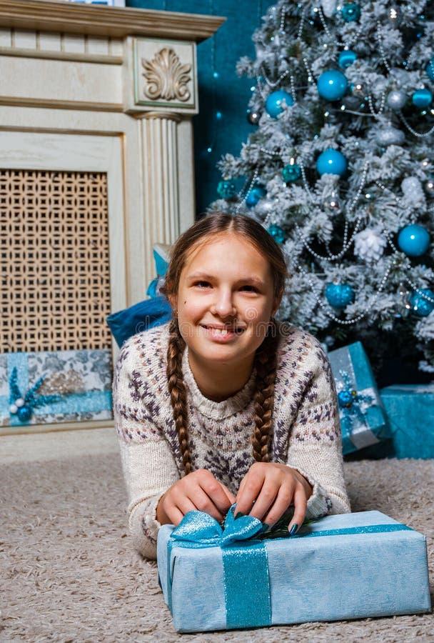 La fille se trouve près d'un arbre de Noël avec le boîte-cadeau de cadeau de Noël photo stock