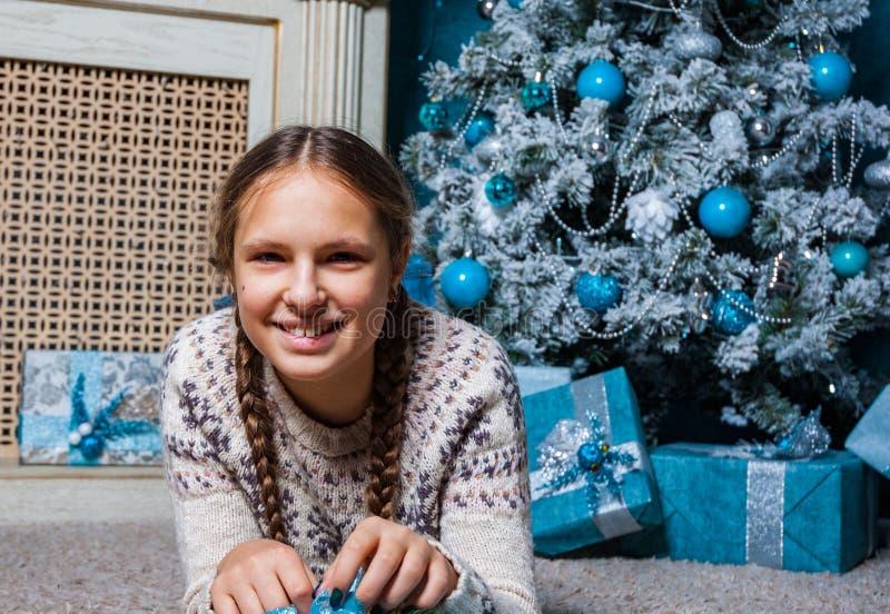 La fille se trouve près d'un arbre de Noël avec le boîte-cadeau de cadeau de Noël image stock