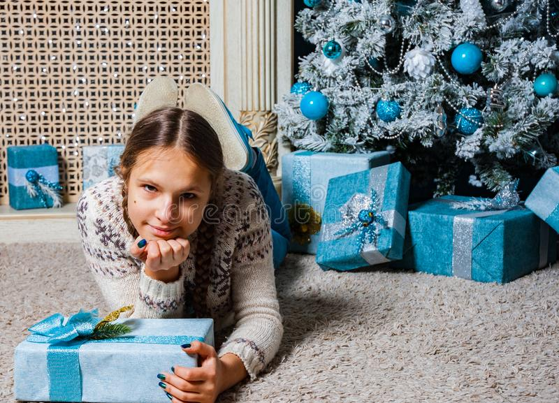 La fille se trouve près d'un arbre de Noël avec le boîte-cadeau de cadeau de Noël image libre de droits