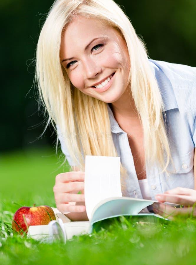 La fille se trouve sur l'herbe verte et lit le livre photo stock