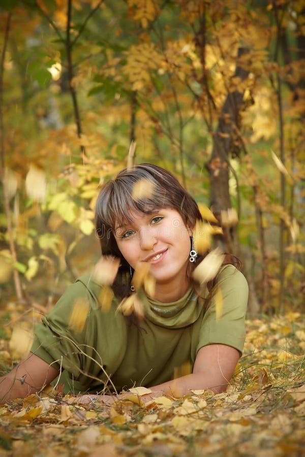 La fille se trouve sur la prise de masse sous des lames d'automne photo libre de droits
