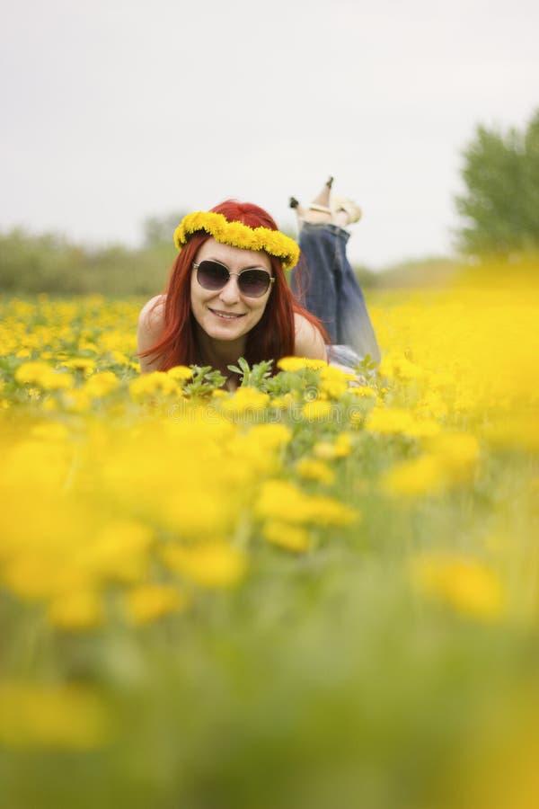 La fille se trouve sur le champ brouillé des pissenlits photographie stock libre de droits