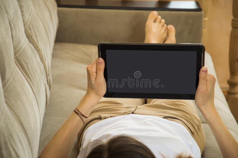 La fille se trouve sur le divan et lit des nouvelles et des messages sur le comprim? photo stock