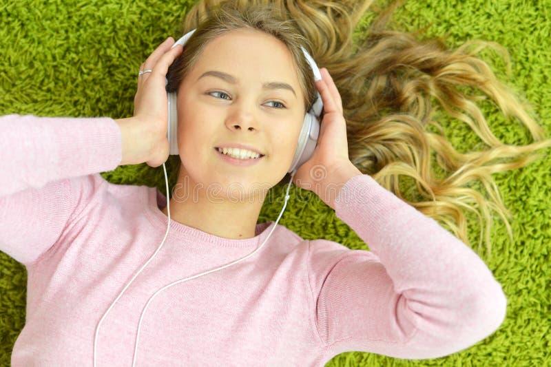 La fille se trouve sur le plancher et écoute la musique photographie stock