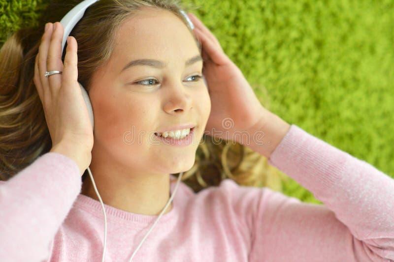 La fille se trouve sur le plancher et écoute la musique image stock