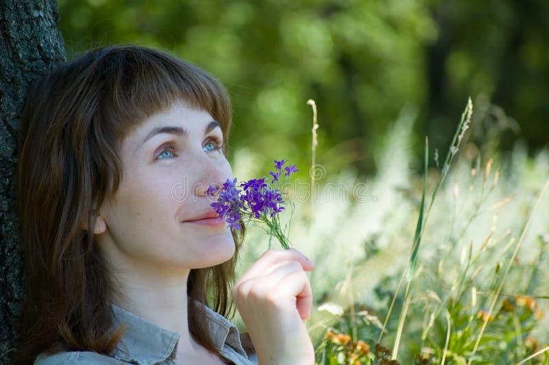 La fille sent des fleurs photographie stock libre de droits