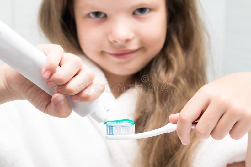 La fille serre la pâte dentifrice sur une brosse à dents pendant la toilette de matin, plan rapproché photo stock