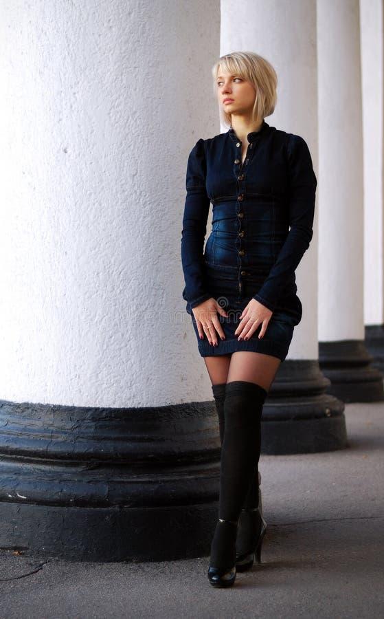 La fille sexy dans de mini jeans rectifient et noircissent des bas photo stock