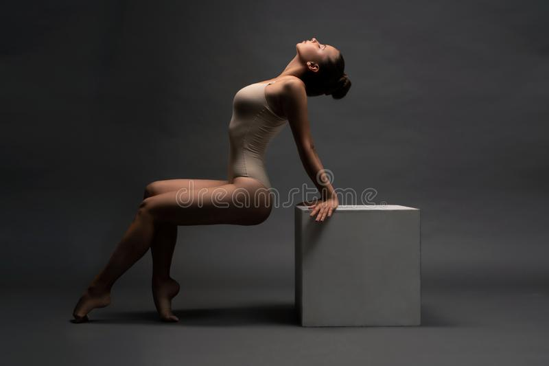 La fille sexy dans le corps beige l'arquant regardent de retour image stock