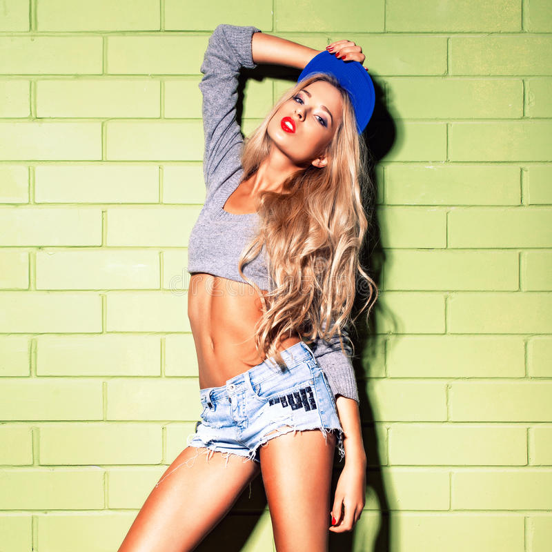 La fille sexy de bronzage dans des jeans courts court-circuite contre le mur de briques vert photos libres de droits