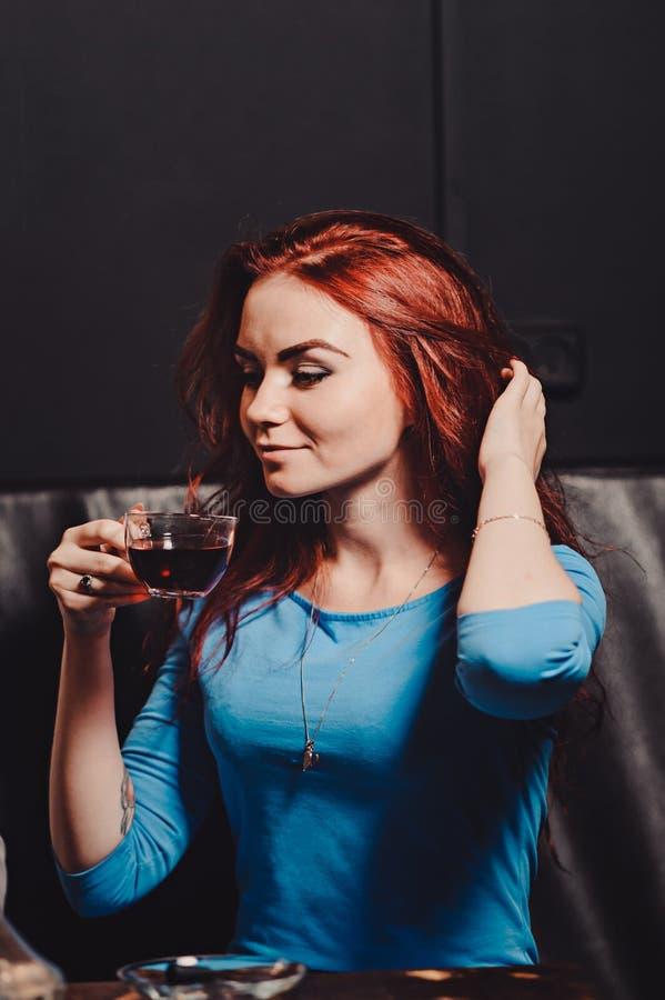 La fille sexy rousse dans un café fumant un narguilé s'est habillée dans un chemisier bleu photographie stock libre de droits