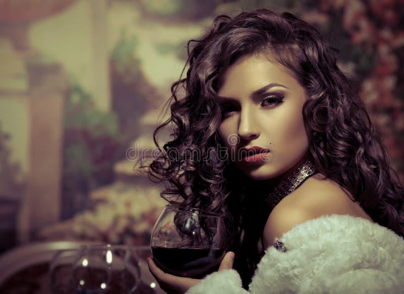 La fille sexy s'asseyent avec du vin dans le manteau de fourrure à la soirée image libre de droits