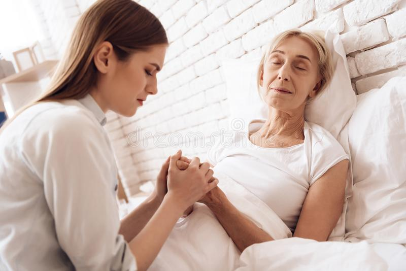 La fille soigne la femme agée à la maison Elles tiennent des mains La femme se sent plus mal photo libre de droits