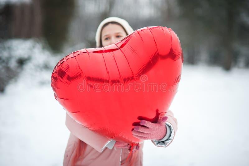La fille sortie heureuse avec le coeur de Valentine monte en ballon extérieur Concept de jour du ` s de Valentine Copiez l'espace photos libres de droits