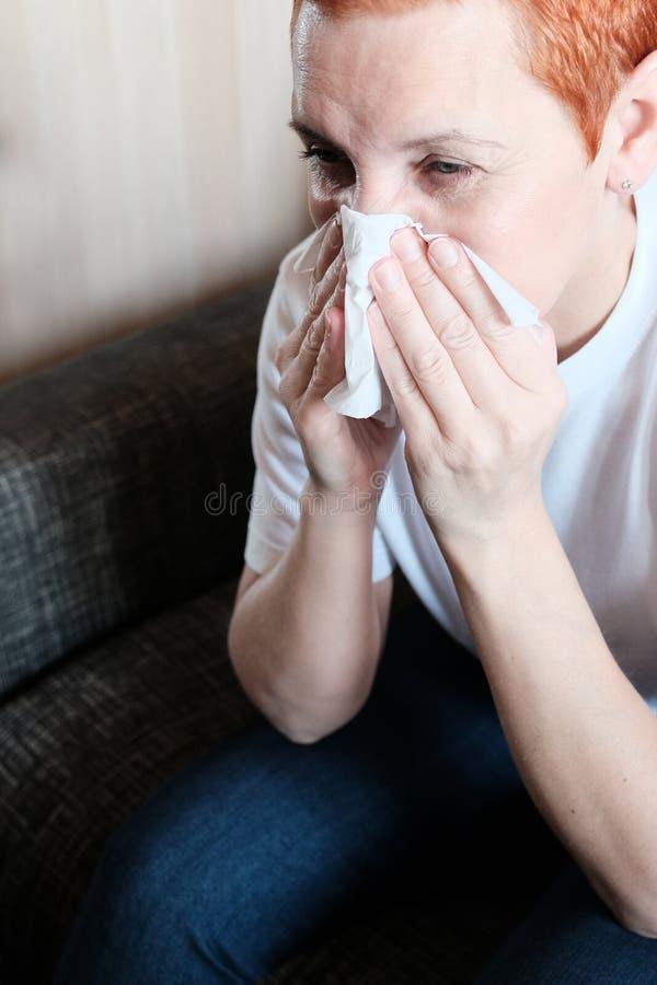 La fille souffre des allergies Il met une serviette de papier à son nez Démanger et éternuer Irritation du nasal images stock