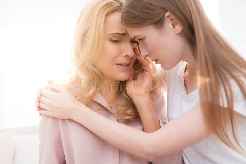 La fille soulage une femme adulte qui pleure images stock
