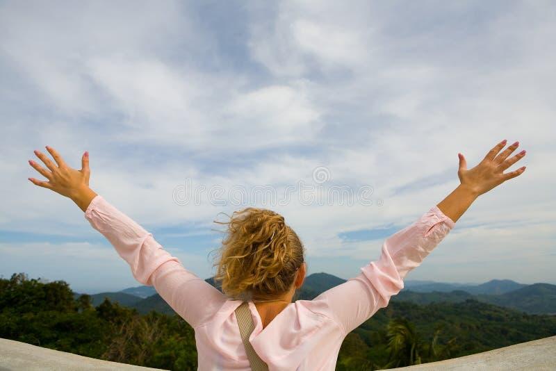 La fille a soulevé ses mains dans différentes directions contre le ciel et les montagnes photo libre de droits