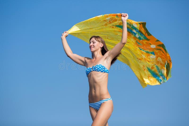 La fille sportive dans le bikini bleu se déplaçant avec des bras a augmenté contre le ciel photos stock
