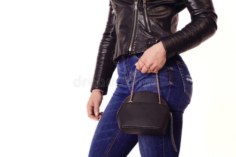 La fille sportive dans la veste en cuir et des jeans tient la bourse sur la chaîne image stock