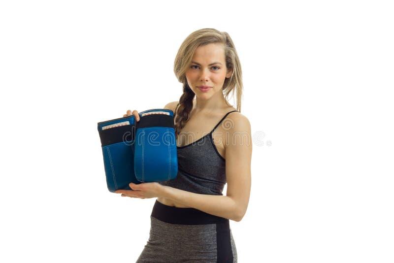 La fille sportive regarde dans l'appareil-photo et des gants de boxe de prises est isolés sur un fond blanc photos stock